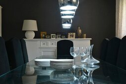 Crockery on glass table under pendant lamps in dining room with dark walls