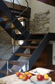 Modern wooden and metal staircase attached to stone wall