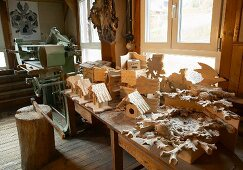 Elaborate cuckoo clock, bird nesting boxes and other carvings in traditional workshop