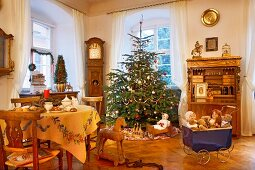 Klassisch geschmückter Weihnachtsbaum und historisches Spielzeug im Wohnraum mit antiken Möbeln