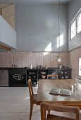 Gallery and kitchen-dining area in double-height interior of old, renovated wooden house