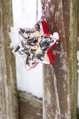 Red star-shaped pastry cutter filled with bird cake hanging from wooden fence