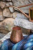Windlicht aus Kupfer mit Lochmuster vor Steinwand