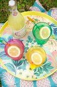 Summer drinks in colourful glasses on floral tray