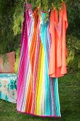 Tunic and striped towel hung from washing line in garden