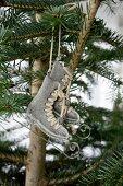 Deko-Schlittschuhe aus Metall hängen an einem Tannenbaum