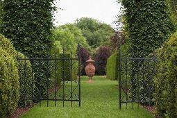 Schmiedeeisernes Tor zwischen hochgewachsenem, geschnittenem Buchs in gepflegtem Rasenstück, Amphore im Hintergrund