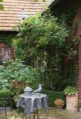 Sommerbeet mit Rosenstrauch an der Ziegelfassade, Gartenmöbel aus Metall und graue Skulpturen