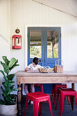 Boy at a rustic wooden table with red classic stools and green plants
