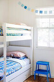 White bunk bed with colorful bed linen and blue step stool in front of window