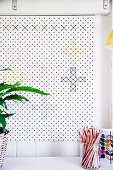 White perforated plate with cross-stitches in different colors as wall decoration, in front of glass with colored pencils