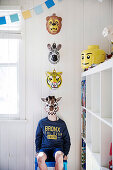 Boy with animal mask sitting on chair in white wood-clad children's room