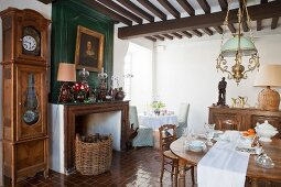 Porcelain crockery on wooden table and antique long-case clock next to open fireplace in dining room
