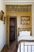 Antique brass bed against wooden wall with interior transom window and view of wooden cupboard in hallway
