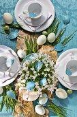 Gedeckter Ostertisch mit Birkenrinde und Grashalmen auf blauer Tapete