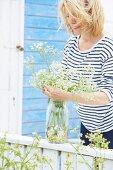 Woman wearing striped top arranging flowers in preserving jar