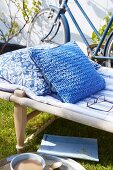 Cushion with blue knitted cover on camp bed in garden