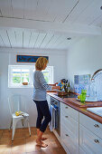 Woman in bright country-house kitchen with wood-beamed ceiling