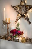 Candles and shiny ornaments below star made from branches and decorated with fairy lights