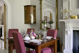 Set table in elegant dining room with open fireplace and large mirror