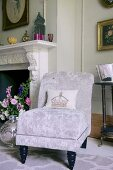 Elegant easy chair with silver velvet cover next to open fireplace
