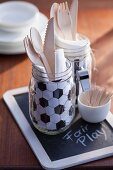Wooden cutlery and football-patterned napkin in glass jar