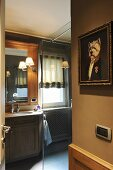 Whimsical oil painting and view into bathroom with glass shower screen, custom washstand and traditional ambiance