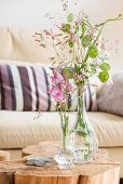 Glass vase of flowers on tree stump table in front of sofa