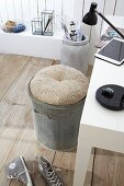 Round cushion on zinc bin used as office chair