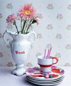 Stack of rose-patterned plates and cup next to flowers in white trophy vase against vintage-style rose-patterned wallpaper