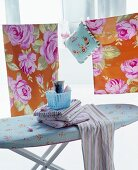 Striped cloths on ironing board in front of rose-patterned bed linen hung on washing line