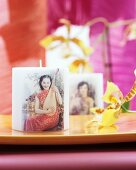 Motivkerzen mit asiatischer Frau und einer Pipa neben Orchideenblüte