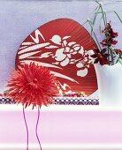 Kunstblume vor einem roten asiatischen Fächer und Orchideen
