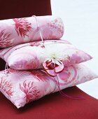 Stapel aus rosafarbenen geblümten Kissen mit Dahlie und Babyschuhen