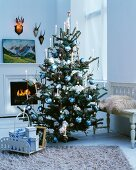 Christmas tree elegantly decorated with blue and white baubles in front of fireplace
