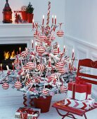 Christmas tree decorated with red and white striped baubles and red lit candles in front of fireplace