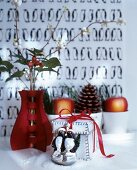 Festive arrangement of red vase, gift box and animal figurine