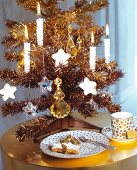 Small, gold artificial Christmas tree decorated with lit candles next to elegant coffee cup and plate on shiny side table