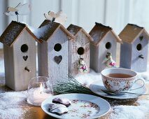 Romantic vintage nesting boxes festively arranged with artificial snow and tea set