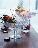 Ice cubes, berries and sparklers in glass goblets