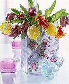 Tulpenstrauß in Geschenktüte mit Rosendekor und österlicher Glasdose mit nostalgischem Flair