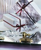 Presents wrapped with lace ribbons in mirrored tray