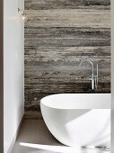 Modern free-standing bathtub against stone wall