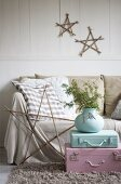 Painted suitcases in front of sofa below wooden stars
