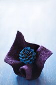 Blue-painted larch cone in fold of purple felt