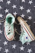 Pale green sneakers on grey rug with pattern of stars