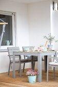Pastel crockery on pale grey table on terrace