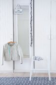 Lady's jacket hung from clothes hanger and step stool in front of white wardrobes