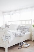 White double bed with headboard and grey and white striped bed linen in Scandinavian-style bedroom