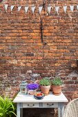 Potted plants on table below bunting on brick exterior wall